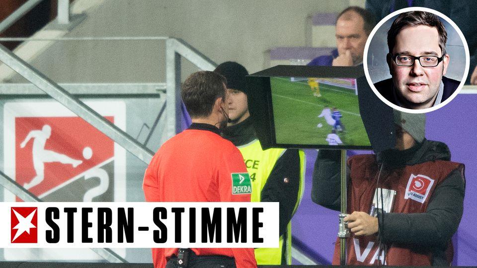 Ein Schiedsrichter steht am Spielfeldrand und schaut sich eine Szene auf einem Monitor an