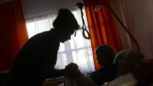 Eine alte Frau wird von einer Pflegerin betreut