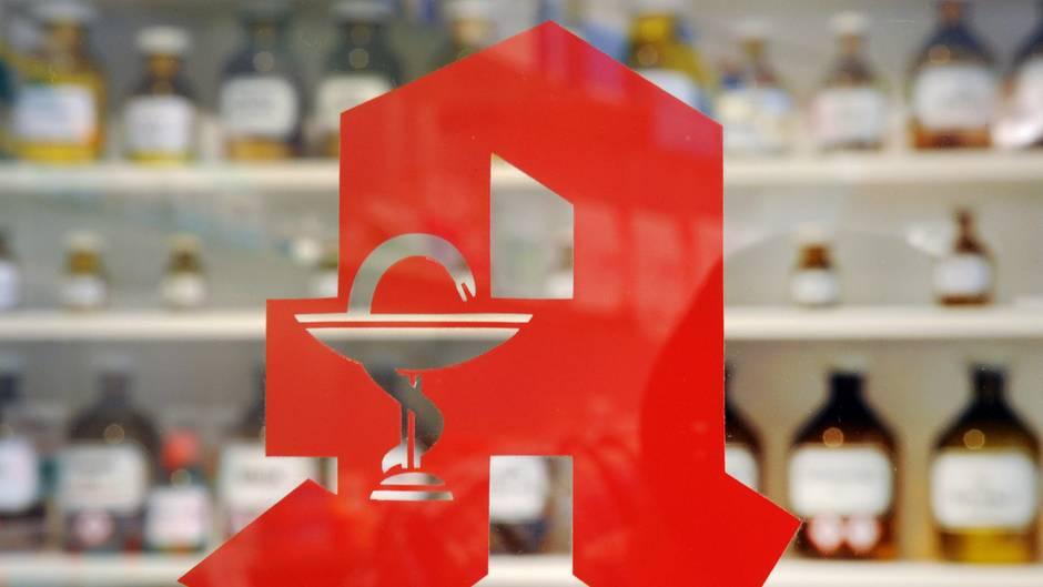 """Auf einer Glasscheibe klebt das rote Apotheken-""""A"""", unscharf im Hintergrund braune Apothekerflaschen in einem Regal"""