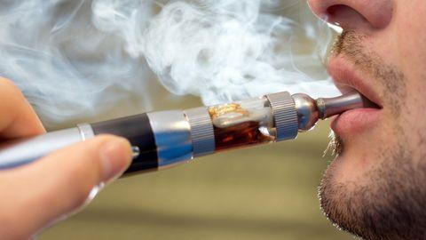 E-Zigarette: Ein junger mann benutzt eine E-Zigarette