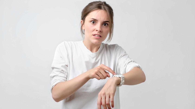 Frau zeigt hektisch auf ihre Uhr