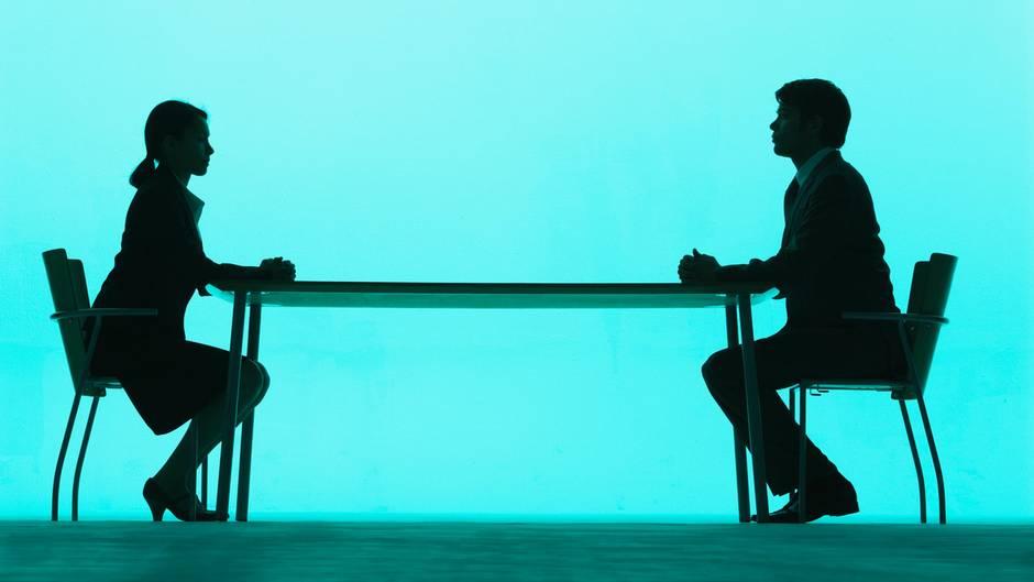 Frau und Mann setzen sich am Tisch gegenüber