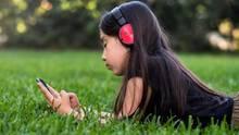 Mädchen spielt auf der Wiese am Handy