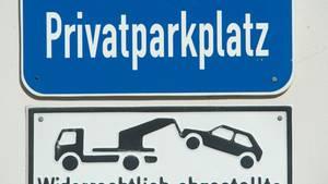 """An einer weißen Wand hängt ein blaues Hinweisschild """"Privatparkplatz"""""""
