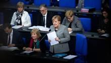 An ihrem Sitzplatz im Bundestag steht Angela Merkel, hält Papiere in den Händen und spricht in ein Mikrofon