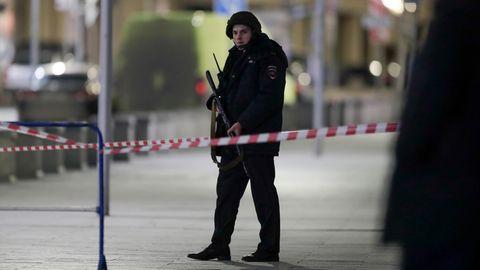 Ein Polizist in Kampfmontur und Helm hält Wache mit seinem Gewehr in den Händen