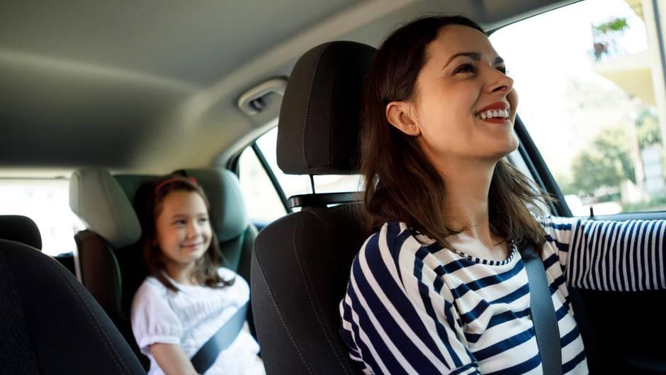 Eine Frau fährt lächelt Auto und sieht im Rückspiegel ihre Tochter an
