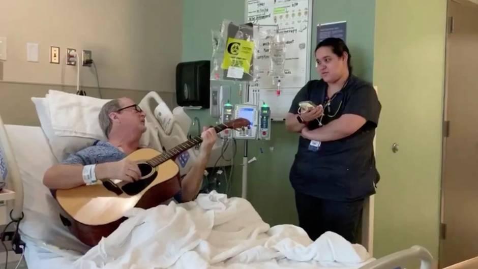 Krankenschwester steht am Bett und singt mit einem Patienten, der Gitarre spielt
