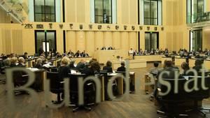 """Durch eine Glasscheibe mit """"Bundesrat""""-Schriftzug ist ein voller Sitzungssaal mit Länderwappen zu sehen"""