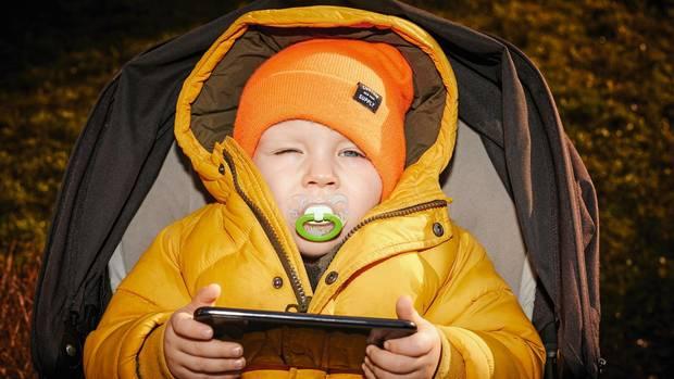 Ein kleines Kind mit Schnuller und Tablet