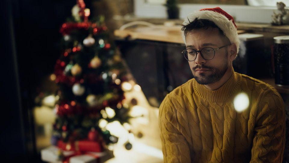 Ein Mann sitzt alleine zu Hause vor einem Weihnachtsbaum