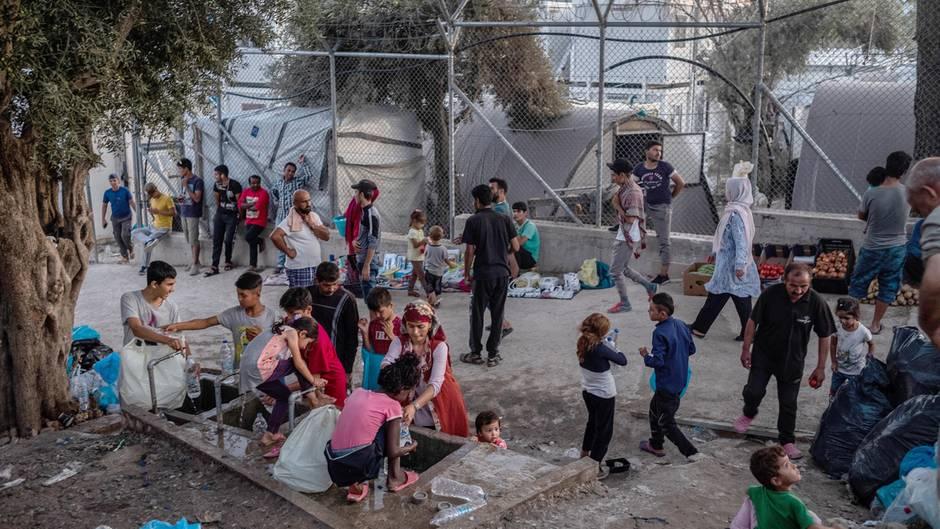 Migranten stehen um eine Wasserstelle und befüllen Flaschen im Flüchtlingslager Moria auf der griechischen Insel Lesbos