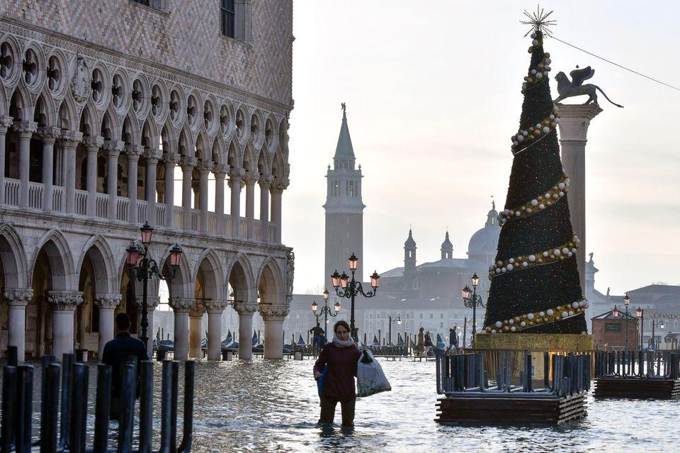 Knietief im Wasser waten auf dem Markusplatz in Venedig