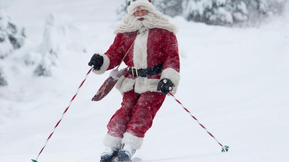 """Ein Mann fährt mit Skiern während des alljährlichen """"Santa Ski"""" durch den Puderschnee"""