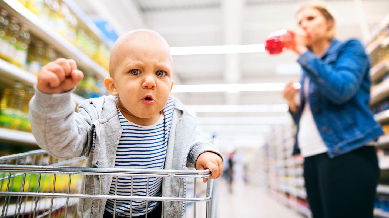 Ein Baby im Einkaufswagen ballt eine Faust