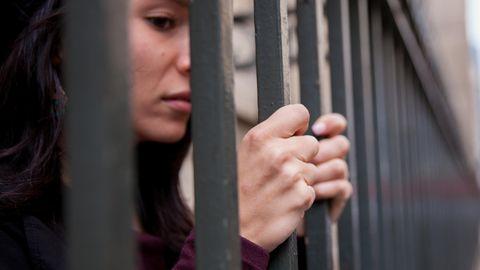 Eine inhaftierte Frau umfasst die Gitterstäbe ihrer Zelle