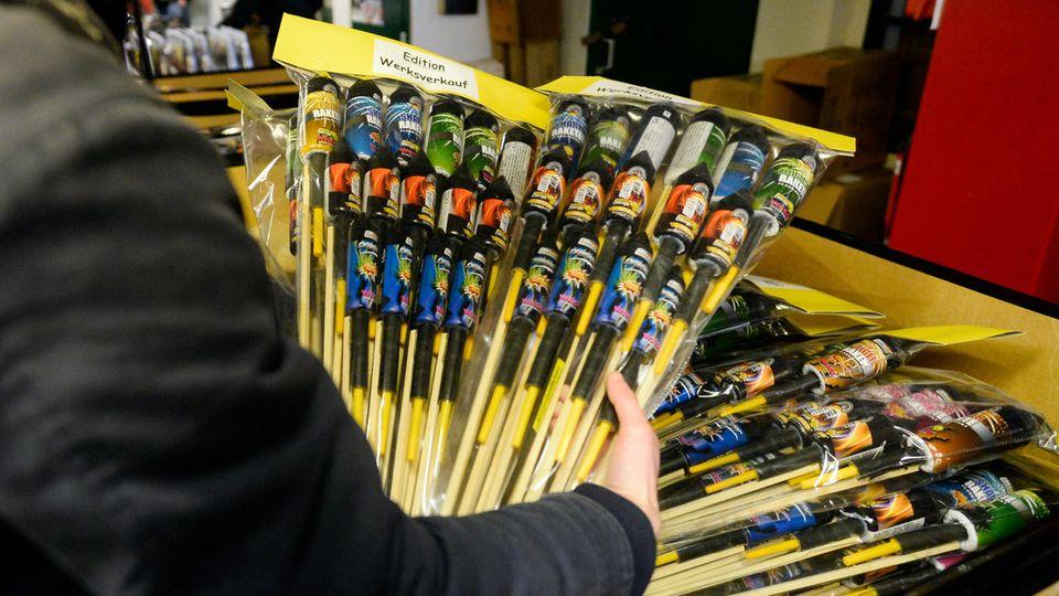 Ein Käufer nimmt abgepackte Feuerwerksraketen beim Werksverkauf des Herstellers WECO