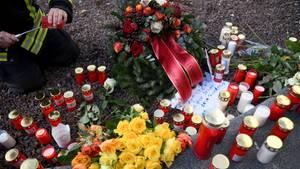 Ein Feuerwehrmann zündet am Königsplatz in Augsburg für seinen toten Kollegen eine Kerze an