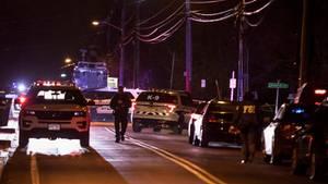 Sicherheitskräfte versammeln sich nach einer Messerstecherei auf einer Straße.