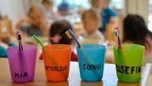 Zahnbürsten und Zahnputzbecher mit den Vornamen der Kinder stehen in einer Kindertagesstätte auf einem Tisch