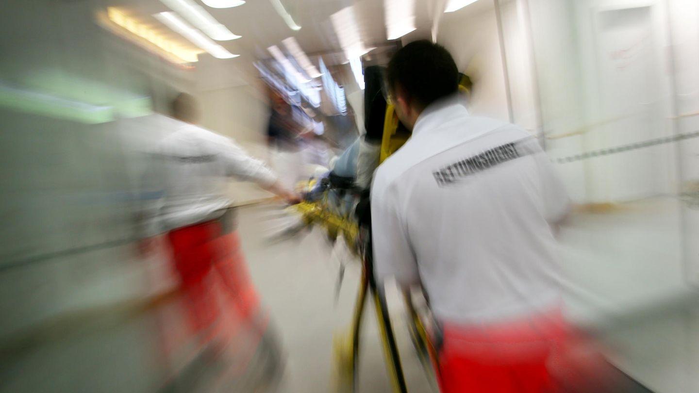 Rettungsassistenten des BRK liefern eine Notfallpatientin auf einer Trage in ein Krankenhaus ein