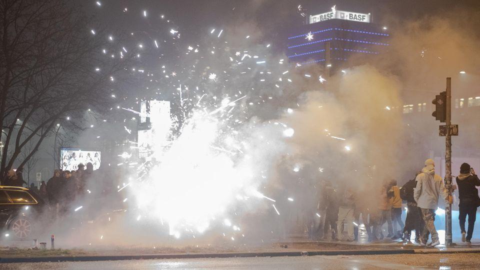 Böller und Raketen steigen in Berlin an der Oberbaumbrücke in die Luft, während Passanten vorbeigehen