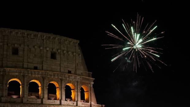 Italien, Rom: Ein Feuerwerk explodiert während der Neujahrsfeierlichkeiten über dem Kolosseum