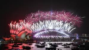Der Sydney Harbour ist in Feuerwerk gehüllt. Im Vordergrund treiben Boote auf dem Wasser