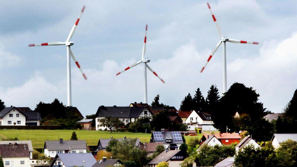 Windräder des Windparks Schöneseiffen drehen sich hinter Wohnhäusern