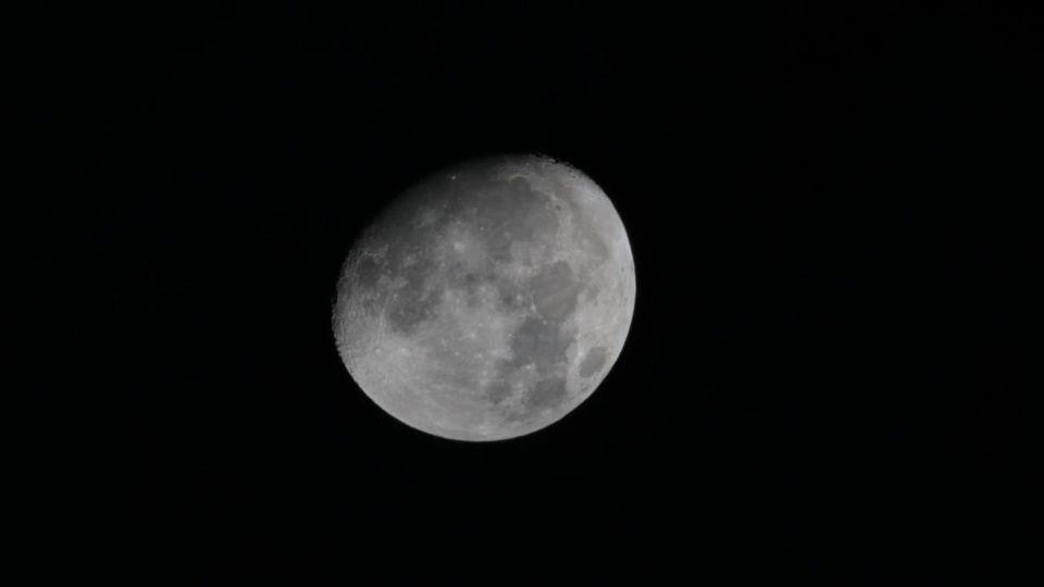 An einem schwarzen Himmel ist der Mond in Großaufnahme zu sehen. Er wirkt grau und seine Krater sind deutlich zu sehen
