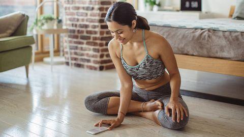 Frau macht Yoga im Schlafzimmer
