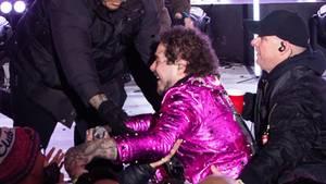Post Malone im pinken Anzug. Security-Mitarbeiter helfen ihm nach seinem Sturz wieder auf die Bühne