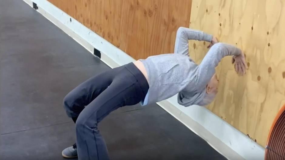 Älterer Mann macht eine Brücke an der Wand einer Sporthalle
