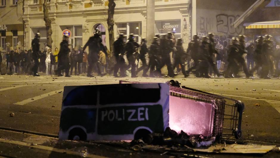 Polizeibeamte passieren in der Silvesternacht in Leipzig-Connewitz einen umgekippten Einkaufswagen