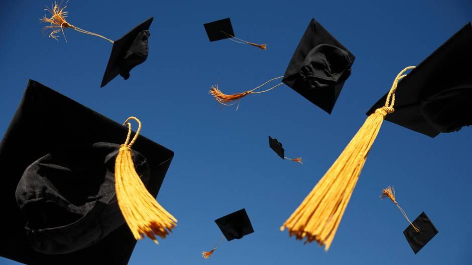 Hüte fliegen auf einer Abschlussfeier in die Luft