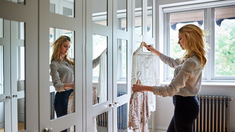 Frau steht vor ihrem Kleiderschrank