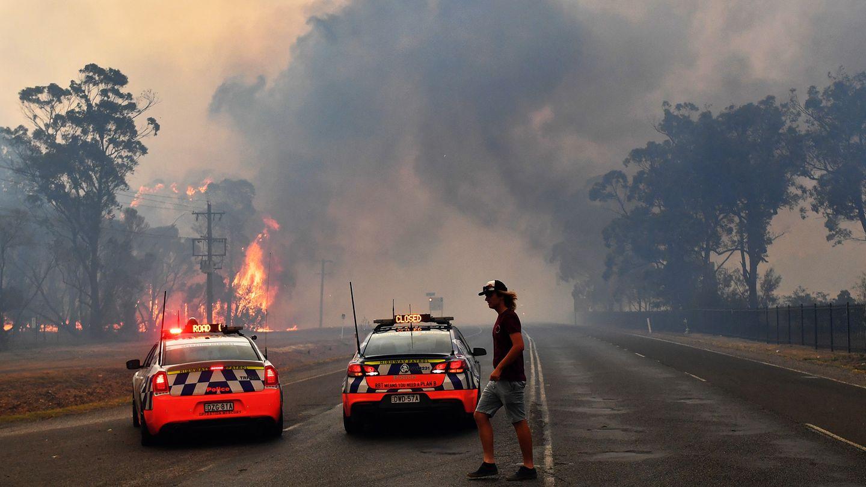 Die Polizei sperrt mit zwei Polizeiautos südwestlich von Sydney eine Straße zu einem Gebiet, das in Flammen steht. Aufgrund der verheerenden Buschbrände ist in Australiens bevölkerungsreichstem Bundesstaat New South Wales erneut der Notstand ausgerufen worden.