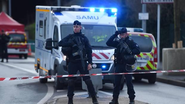 Polizisten stehen vor einem Krankenwagen