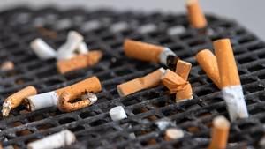 Zahlreiche Zigarettenstummel liegen in einem Aschenbecher vor einem Büro
