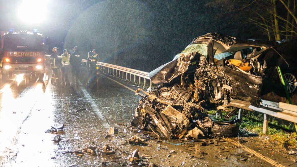 Das völlig zerstörte Wrack eines Fahrzeuges hängt in der Leitplanke der der Bundesstraße 456 im Hochtaunuskreis