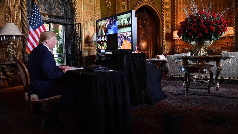 Trump vor einem großen Bildschirm