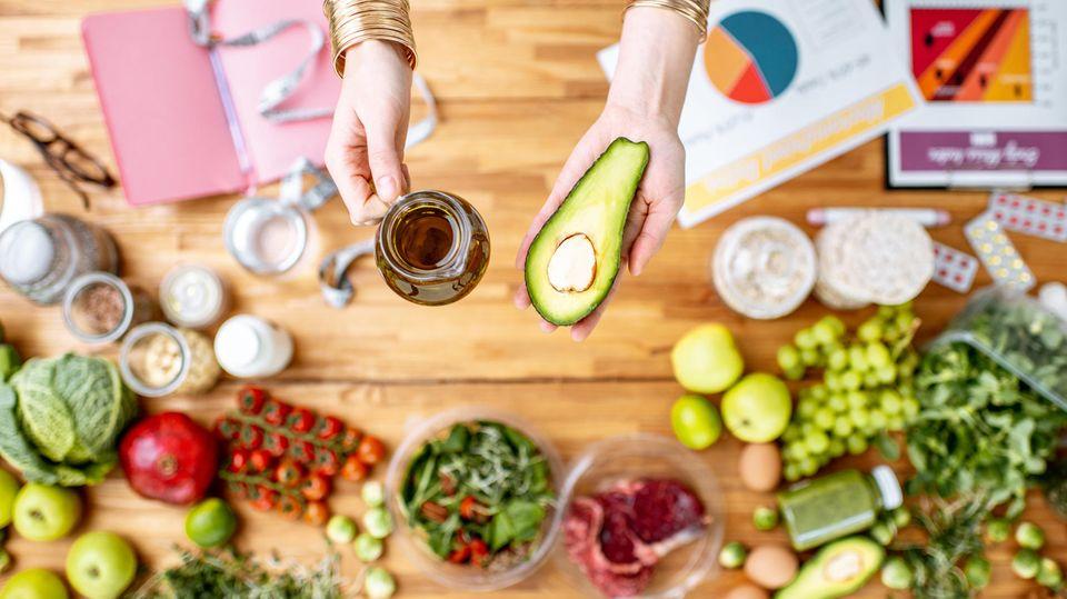 Frau hält Avocado und Öl