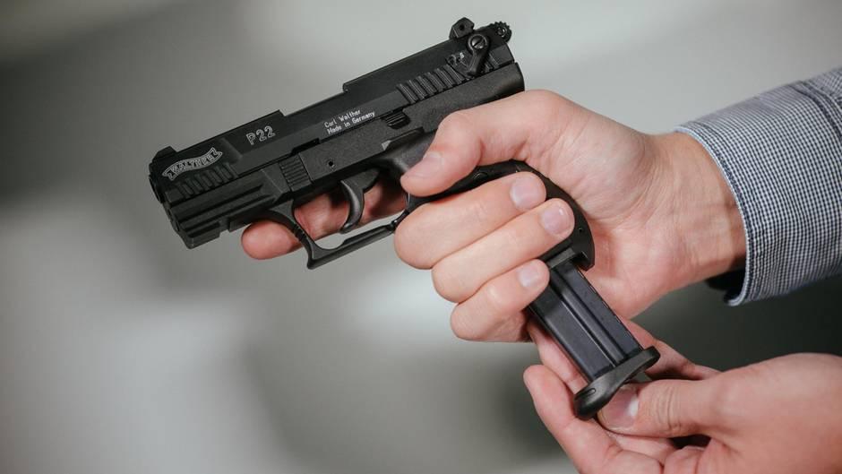 Hände laden eine Schreckschuss-Pistole «Walther P22» mit einem Magazin