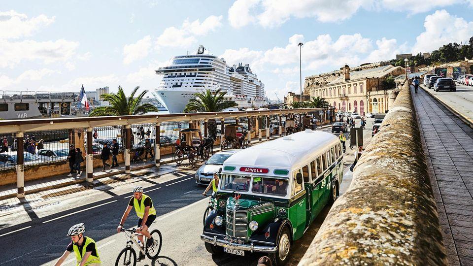 Im Hintergrund: die MSC Grandiosa. Im Vordergrund: Eine befahrene Straße