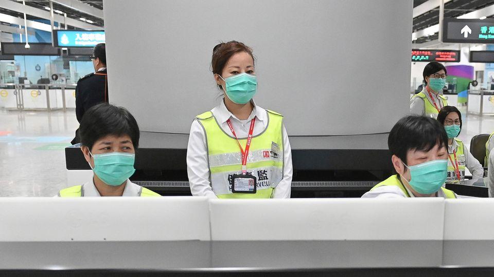 Mitarbeiter der Gesundheitsbehörden untersuchen Reisende am Hongkonger Bahnhof West Kowloon Stationauf ihren Gesundheitszustand