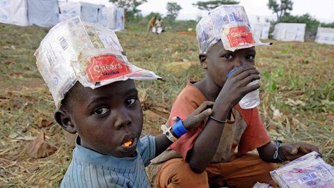 Zwei Flüchtlingsjungen in Uganda trinken und essen