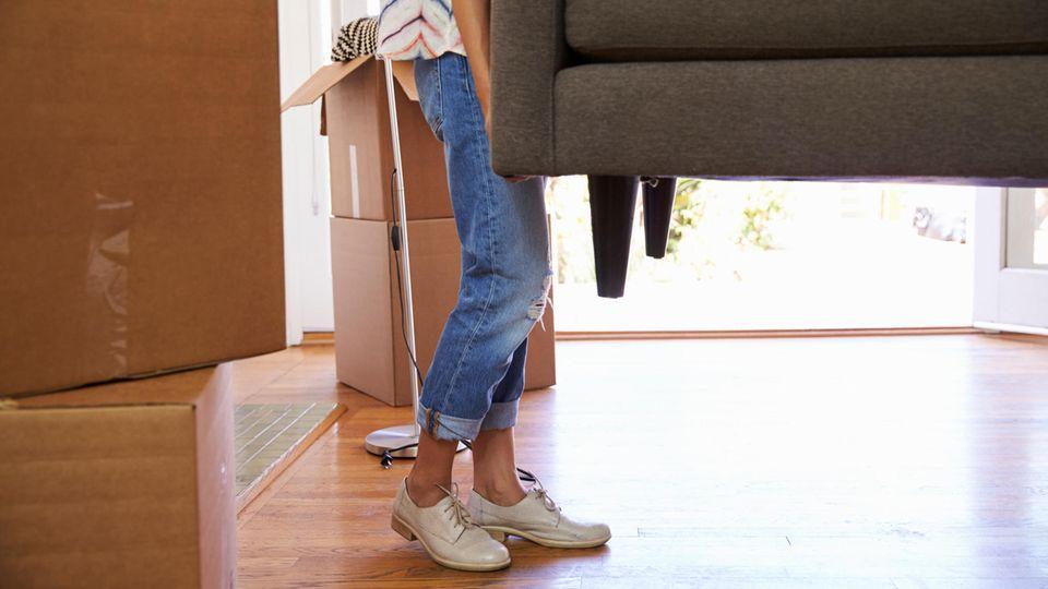 Eine junge Frau trägt Kisten in eine Wohnung