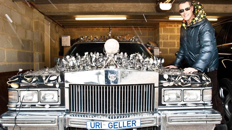 Uri Geller steht neben seinem Cadillac, auf dem Löffel befestigt sind