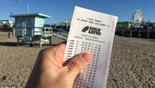Eine Hand zeigt einen Lottoschein am Strand