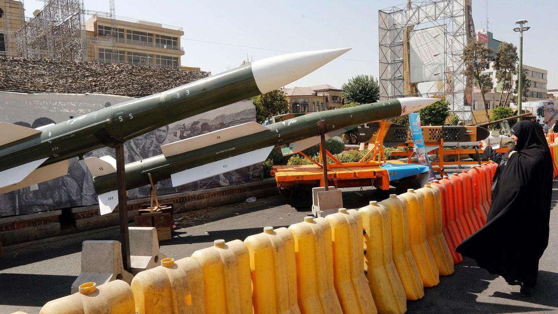 Eine Iranerin schaut sich mehrere ausgestellte Taer-2-Raketen an